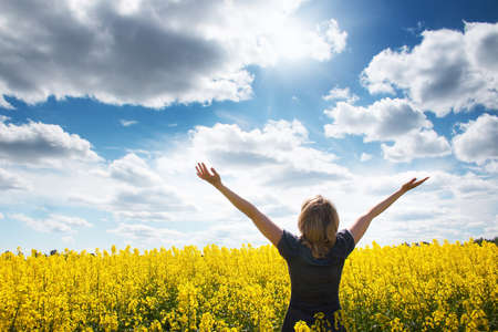 Foto de Young woman on field with yellow flowers - Imagen libre de derechos