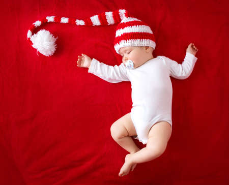 Photo for little baby in knitted red whitey hat on red blanket - Royalty Free Image