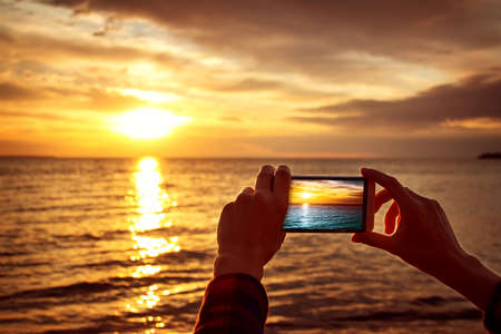Photo pour woman hands holding mobile phone at sunset - image libre de droit