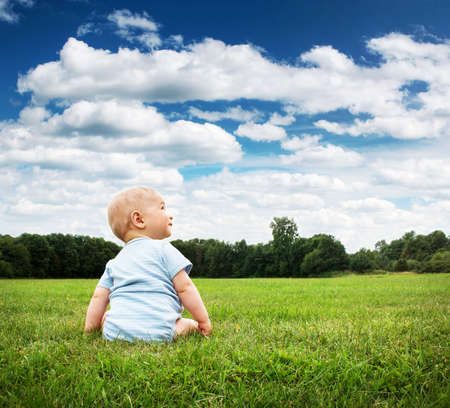 Foto de Little baby boy sitting on the grass - Imagen libre de derechos