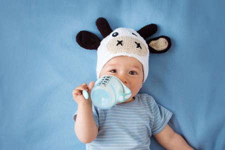 Foto de cute baby in a cow hat drinking milk - Imagen libre de derechos