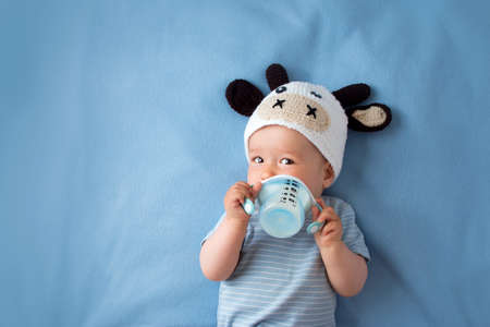 Photo pour cute baby in a cow hat drinking milk - image libre de droit