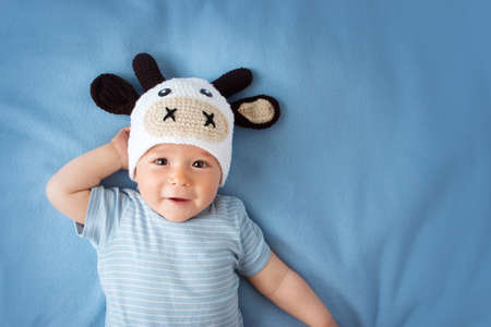 Photo for cute baby in a cow hat on blue blanket - Royalty Free Image
