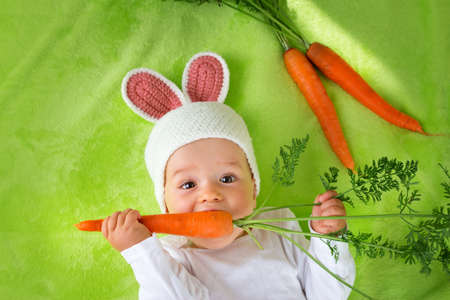 Photo for Baby in rabbit hat eating fresh carrot - Royalty Free Image
