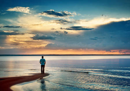 Foto per Alone man stamding at the sea in twilight - Immagine Royalty Free