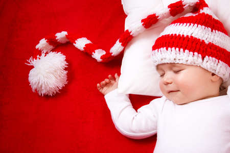 Foto de Sleepy baby on red blanket in knitted hat - Imagen libre de derechos