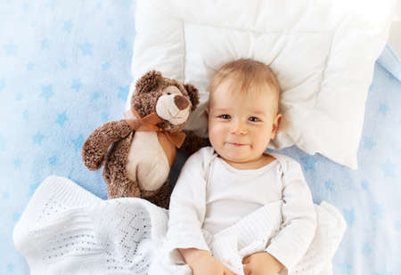 Photo for One year old baby lying in bed with a plush teddy bear - Royalty Free Image