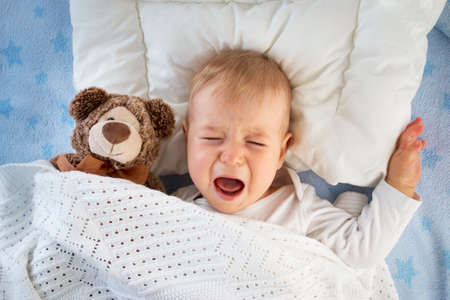 Photo for One year old baby crying in bed with a teddy bear - Royalty Free Image