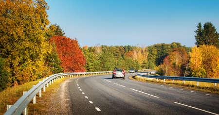 Photo pour cars moving on a highway road in autumnal landscape - image libre de droit
