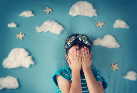 Foto de boy lying on blanket with white clouds in pilot glasses - Imagen libre de derechos