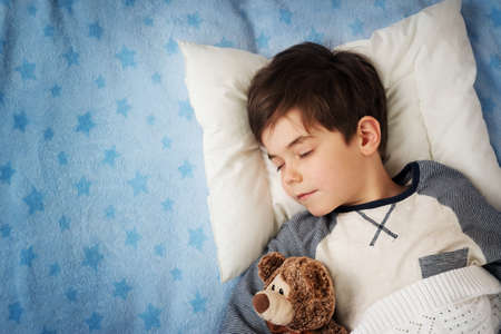 Foto de six years old child sleeping in bed on pillow with alarm clock and a teddy bear - Imagen libre de derechos
