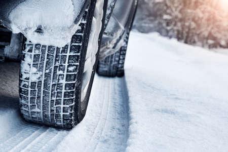 Foto de Closeup of car tires in winter on the road covered with snow - Imagen libre de derechos