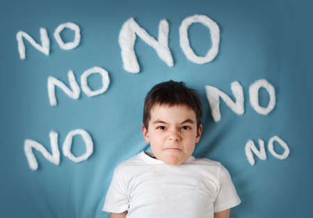 Foto de bad boy on blue blanket background. Angry child with no words around - Imagen libre de derechos