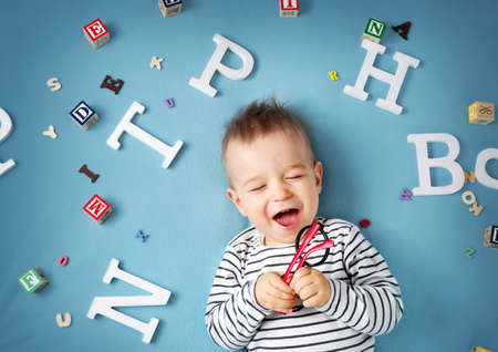 Photo pour One year old child lying with spectacles and letters on blue background - image libre de droit