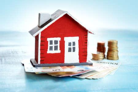 Foto de Red house model on wooden background with banknotes and coins - Imagen libre de derechos