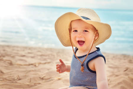 Photo for one year old boy sitting at the beach in straw hat - Royalty Free Image