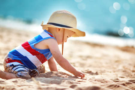 Foto de one year old boy playing at the beach in straw hat. Child on family vacations at sea - Imagen libre de derechos