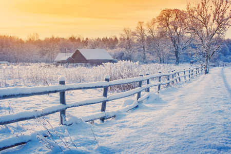 Foto de Rural house with a fence in winter. Village after snowfall - Imagen libre de derechos