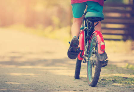Foto de child on a bicycle at asphalt road in early morning - Imagen libre de derechos