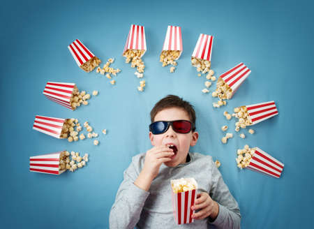 Photo pour Child lying on blue background in 3d glasses and watching tv - image libre de droit