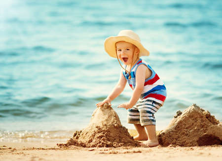 Photo for little boy walking at the beach in straw hat - Royalty Free Image