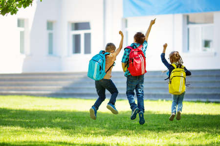 Photo pour Children with rucksacks jumping in the park near school - image libre de droit