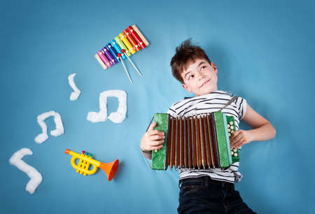 Photo for boy on blue blanket background with accordion - Royalty Free Image