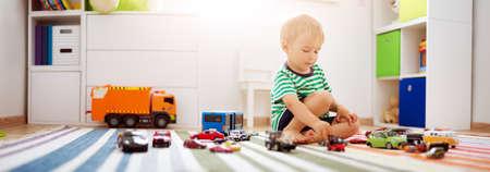 Photo pour Little child playing with toy cars - image libre de droit