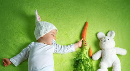 Foto de Baby in rabbit hat eating carrot - Imagen libre de derechos