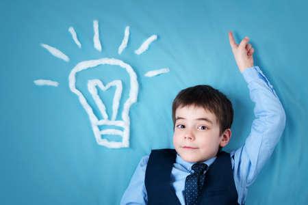 Foto de seven years old boy and a bulb near. Child with an idea - Imagen libre de derechos