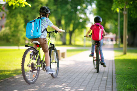 Photo pour Children with rucksacks riding on bikes in the park near school - image libre de droit