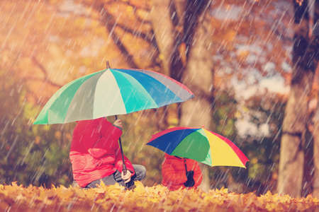 Photo for children with umbrellas in beautiful autumnal day - Royalty Free Image