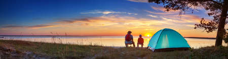 Foto de Family resting with tent in nature at sunset - Imagen libre de derechos