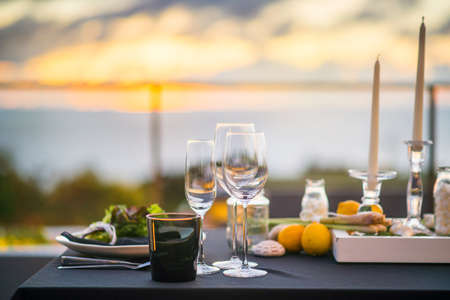 Photo pour Empty glasses set in restaurant Dinner table outdoors at sunset - image libre de droit