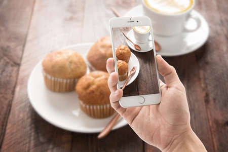 Photo for Taking photo of muffin and coffee on wooden table. - Royalty Free Image