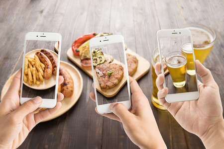 Photo pour friends using smartphones to take photos of sausage and pork chop and beer. - image libre de droit