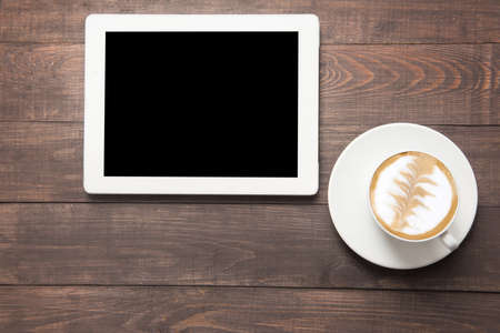 Foto de Digital tablet and coffee cup on wooden background. - Imagen libre de derechos