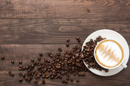 Foto de Coffee cup and coffee beans on wooden background. Top view. - Imagen libre de derechos