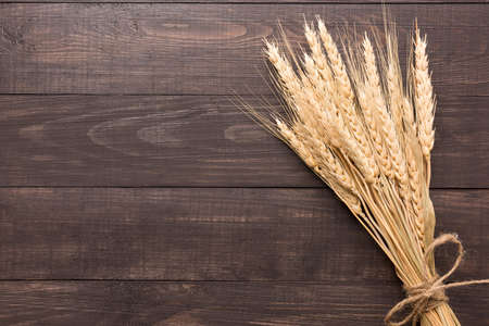 Photo for Wheat ears on the wooden background. Top view. - Royalty Free Image