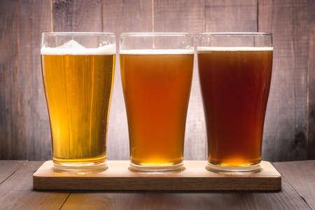 Foto de Assortment of beer glasses on a wooden table. - Imagen libre de derechos