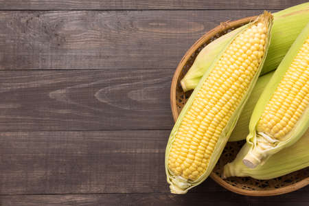 Foto de Fresh organic yellow sweet corn on wooden table. Top view. - Imagen libre de derechos