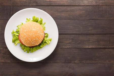 Foto de Top view BBQ burger on white dish on wooden background. - Imagen libre de derechos