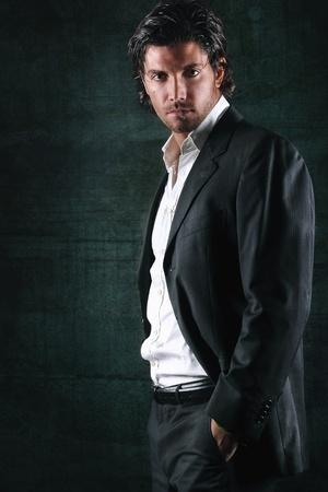 Photo for Drama light on handsome model in elegant dress . Dark textured background - Royalty Free Image