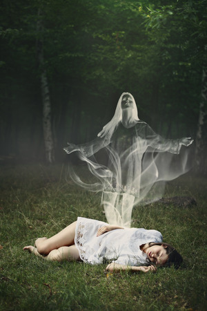 Photo for Soul of a sleeping woman leaving her body in a forest  . Surreal and halloween concept - Royalty Free Image