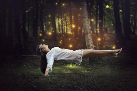 Foto de Woman levitation in the forest surrounded by fairies . Fantasy and surreal - Imagen libre de derechos