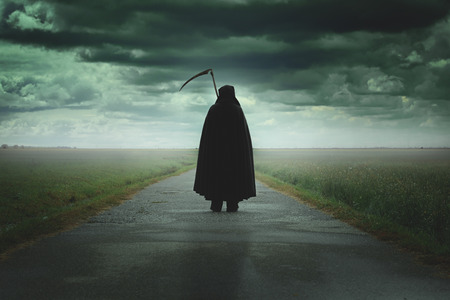 Photo for Grim reaper walking on a dark desolate road .Halloween and death - Royalty Free Image