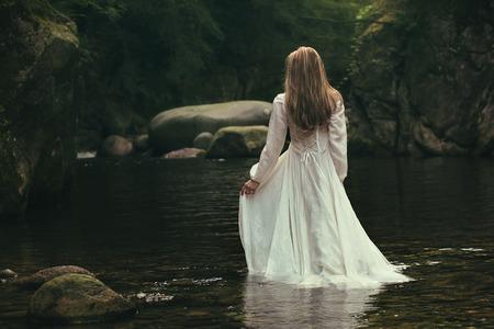 Photo pour Romantic woman walks into a green stream. Ethereal and dreamy - image libre de droit