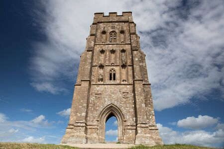 Tourists exploring the ruins of St. Michael\'s Tower at the top of glastonbury tor in somerest england