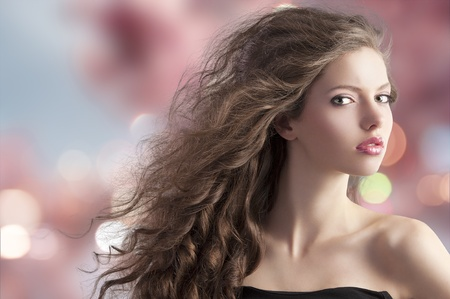 beauty fashion portrait of a very young cute brunette with long curly hair with hairstyle flying in the wind on cherry blossom bokeh background