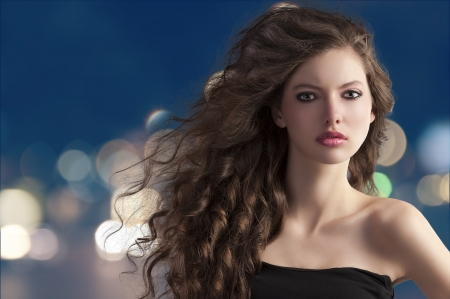 Photo pour beauty fashion portrait of a very young cute brunette with long curly hair with hairstyle flying in the wind on city light bokeh - image libre de droit